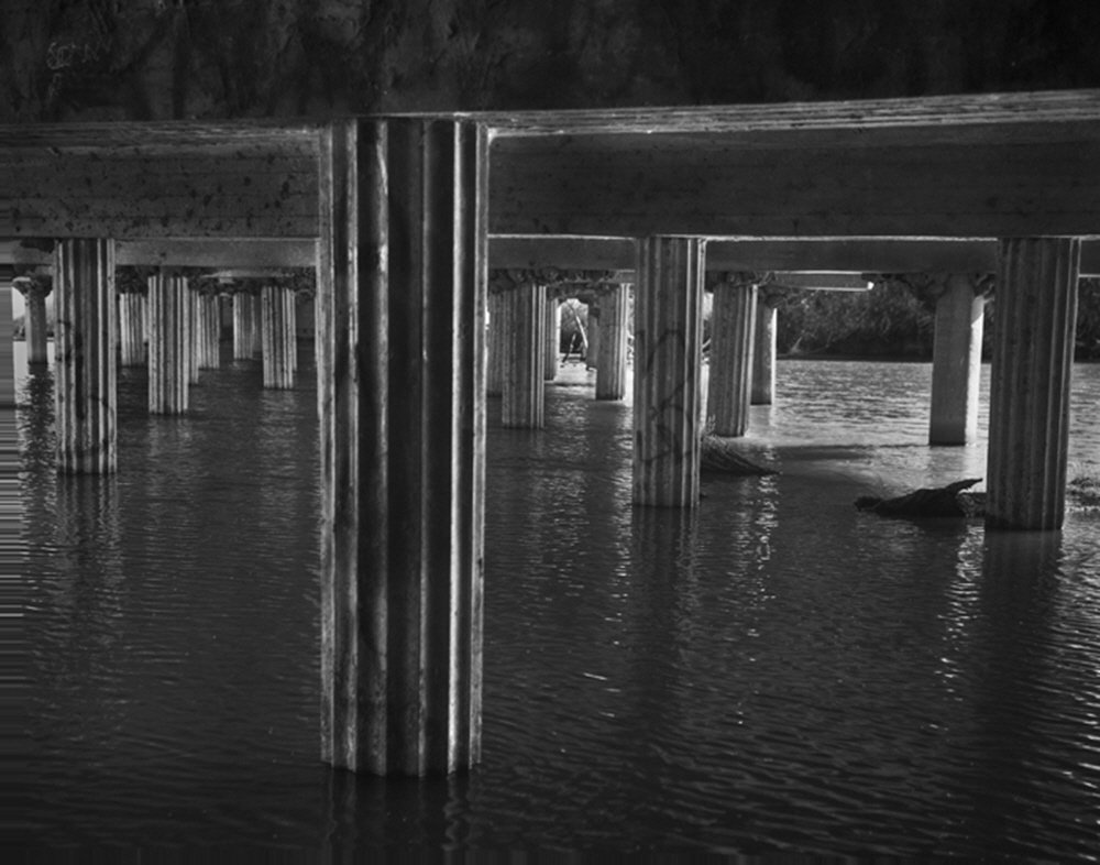 Looking like columns from ancient Rome, the footings for the State Route 41 Bridge near Stratford, California, stand like sentinels as the river transforms into canals.
