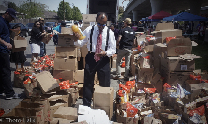 Volunteer Roger Razo of Fresno, is surrounded by bags of food as he sorts out boxes of orange juice to be given away during the Tower District Outreach, part of the Luis Palau City Fest event.