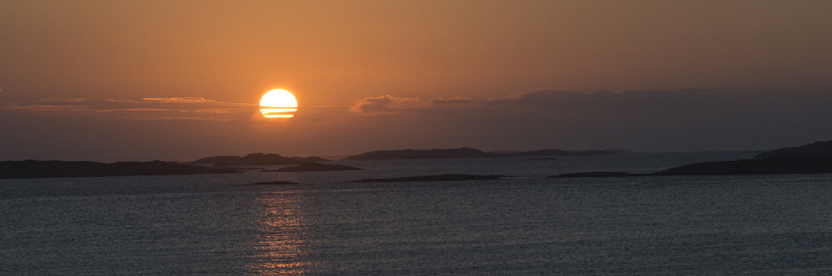 The archipelago of Traena is a string of very small, uninhabitied islands miles off  the Norwegian Coast.  Husoy, the largest island has a population of under 500.  Here the Midnight Sun sets amongst the hundreds of small rock islands.